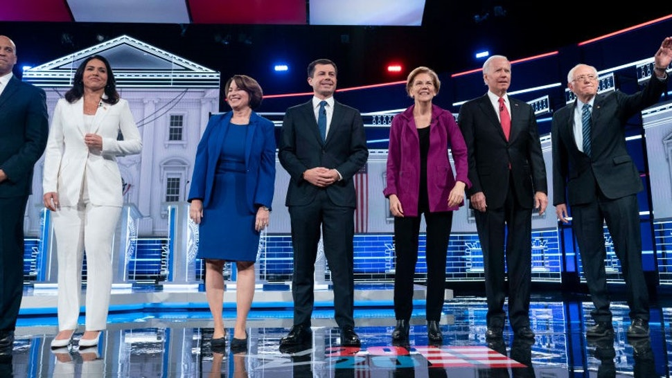 ATLANTA, GEORGIA - NOVEMBER 20: Presidential candidates Sen. Cory Booker (D-N.J.), Rep. Tulsi Gabbard (D-Hawaii), Sen. Amy Klobuchar (D-Minn.), South Bend, Ind., Mayor Pete Buttigieg, Sen. Elizabeth Warren (D-Mass.), Former vice president Joe Biden, and Sen. Bernie Sanders (I-Vt.) appear on stage at the start of he Democratic presidential debate at Tyler Perry Studios on Wednesday, November 20, 2019, in Atlanta, Georgia. The 10 qualifying candidates participated in the campaign seasons fifth debate, hosted by The Washington Post via Getty Images and MSNBC.(Photo by