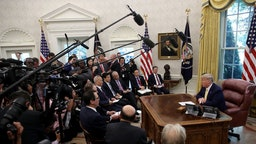 """U.S. President Donald Trump meets with Chinese Vice Premier Liu He and members of the trade negotiation teams while announcing a """"phase one"""" trade agreement with China in the Oval Office at the White House October 11, 2019 in Washington, DC. China and the United States have slapped each other with hundreds of billions of dollars in tariffs since the current trade war began between the world's two largest national economies in 2018."""