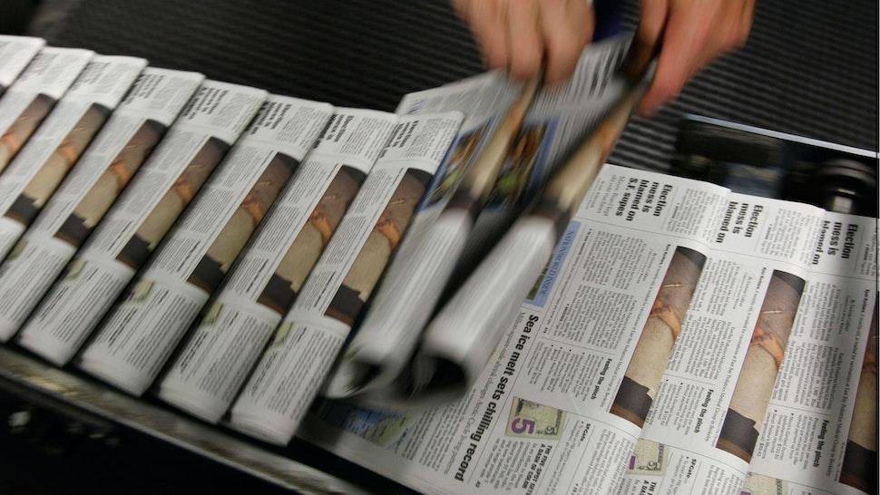 San Francisco Chronicle journeyman pressman Ray Lussier pulls two freshly printed copies of the Chronicle at one of the Chronicle's printing facilities September 20, 2007 in San Francisco, California.