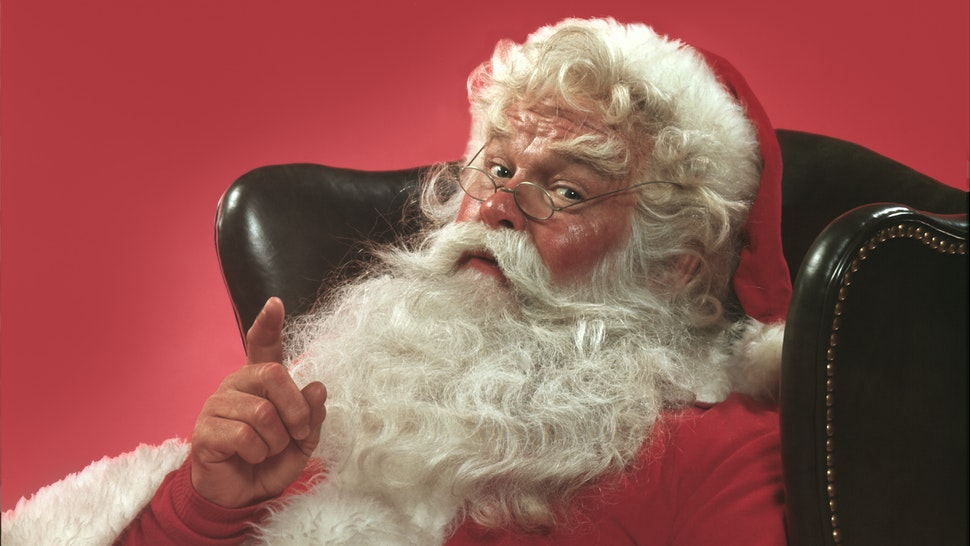 Portrait of Santa Claus sitting in a leather armchair raising one hand in a knowing gesture, 1980. United States.