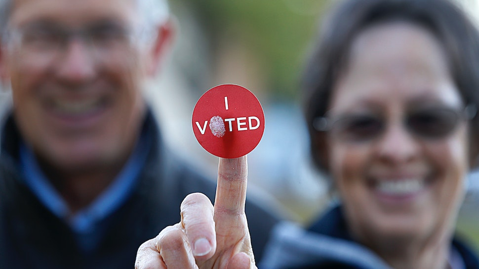 "A couple shows off their ""I Voted"" sticker as they leave Wasatch Elementary school after casting their ballot in the presidential election on November 8, 2016 in Provo, Utah."