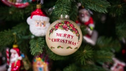 A bauble emblazoned with Merry Christmas hangs from a Christmas tree on display during the opening day of the Christmas Shop in the Selfridges Plc department store in London, U.K., on Monday, Aug. 1, 2016.