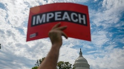 "A protester holds up a sign reading ""impeach"" outside the US Capitol building during the ""People's Rally for Impeachment"" on Capitol Hill in Washington, DC on September 26, 2019."