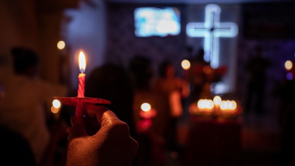 Christians hold candles during Christmas Eve mass at a church on December 25, 2018 in Carita, Banten province, Indonesia.