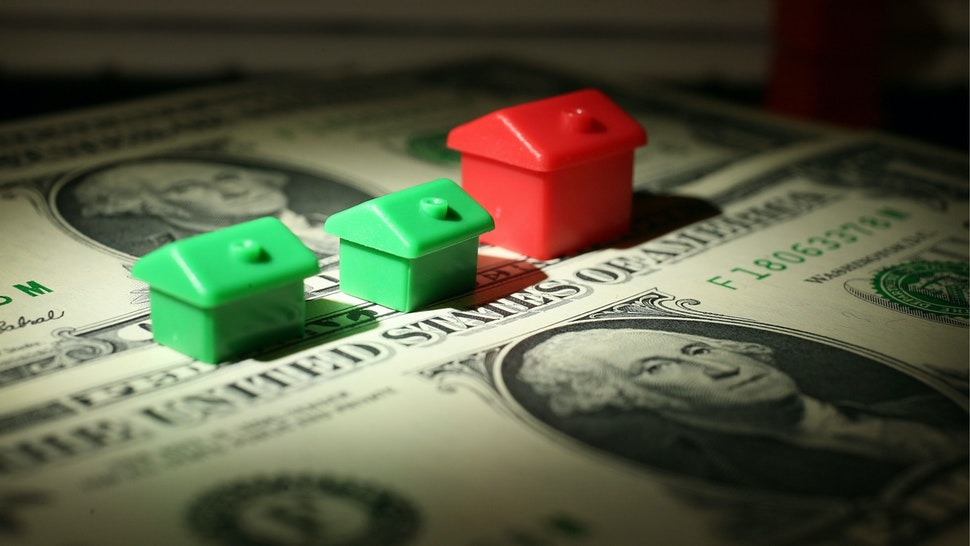 In this photo illustration miniature houses from a Monopoly board game can be seen next to American Dollar notes on October 23, 2008 in Manchester, England.