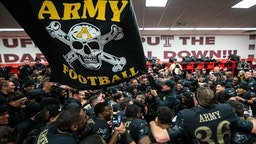 Jeff Monken, Head Coach of the Army Black Knights waves a flag in the locker room after defeating the Navy Midshipmen at Lincoln Financial Field on December 8, 2018 in Philadelphia, Pennsylvania. (Photo by Dustin Satloff/Getty Images)