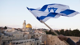 Israelis wave their national flags during a march next to the Western Wall on May 13, 2018 in Jerusalem, Israel.