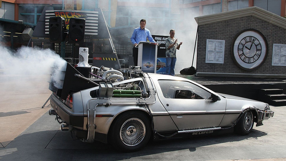 "Actor Christopher Lloyd (in passenger seat) arrives in a DeLorean car at Universal Studios Hollywood's ""Back to the Future - The Ride"" in University City, California, 02 August 2007. Lloyd, who portrayed Doc Brown in the 1985 film ""Back to the Future,"" made the apearence to mark a month-long countdown to the closure of the 14-year-old ride. The DeLorean Motor Co. (Texas), a suburban Houston company that rebuilds DeLoreans, recently announced plans to manufacture a limited number of new Deloreans in 2008. The last DeLorean rolled off the assembly line in Northern Ireland in 1982. On the podium are ""Back to the Future"" writer and co-creator Bob Gale (R) and Universal Studios Hollywood's Chris MacKenzie (L). AFP PHOTO / ROBYN BECK (Photo credit should read ROBYN BECK/AFP via Getty Images)"