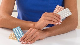 Woman holding contraceptive pills.