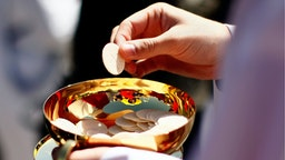 A priest holds a Holy Communion wafer as Pope Benedict XVI celebrates Mass at Nationals Park April 17, 2008 in Washington, DC.