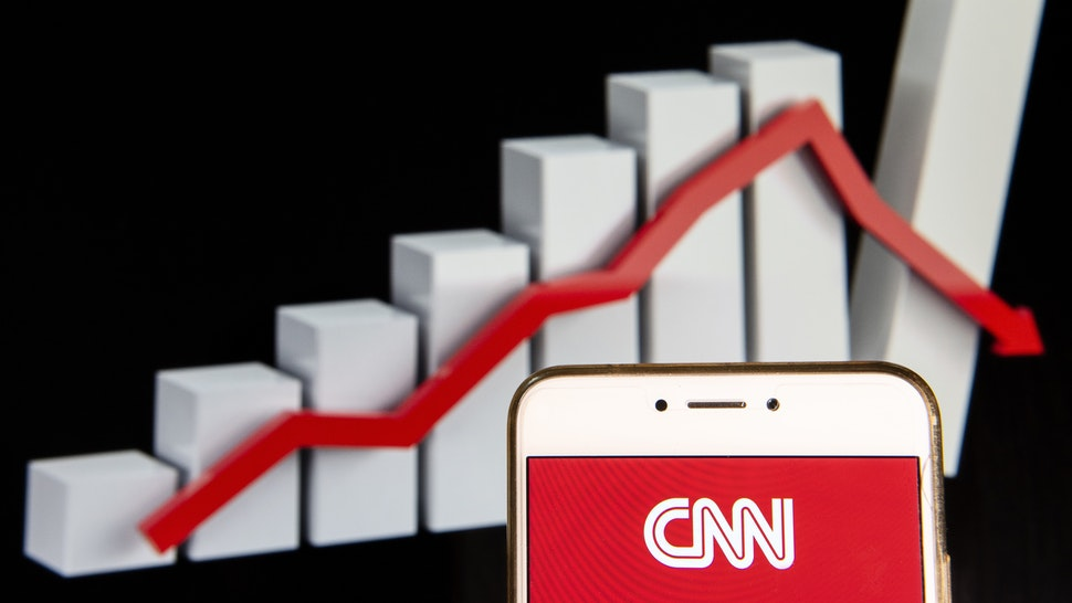 In this photo illustration, the CNN logo is seen displayed on an Android mobile device with a decline loses graph in the background.