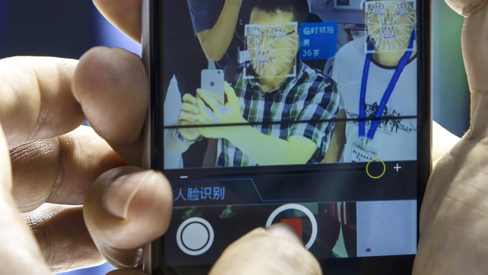 An attendee uses his smartphone to record a facial-recognition demonstration on himself at the Beijing Megvii Co. booth at the MWC Shanghai exhibition in Shanghai, China, on Thursday, June 27, 2019. The Shanghai event is modeled after a bigger annual industry show in Barcelona.