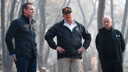 "US President Donald Trump (C) looks on with Governor of California Jerry Brown (R) and Lieutenant Governor of California, Gavin Newsom, as they view damage from wildfires in Paradise, California on November 17, 2018. - President Donald Trump arrived in California to meet with officials, victims and the ""unbelievably brave"" firefighters there, as more than 1,000 people remain listed as missing in the worst-ever wildfire to hit the US state. (Photo by SAUL LOEB / AFP) (Photo credit should read SAUL LOEB/AFP via Getty Images)"