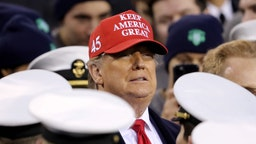 U.S. President Donald Trump stands with the Navy side of the field to start the second half of the game between the Army Black Knights and the Navy Midshipmen at Lincoln Financial Field on December 14, 2019 in Philadelphia, Pennsylvania. (Photo by Elsa/Getty Images)