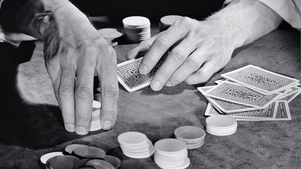 1930s 1940s 1950s Man Hands Gambler Playing Game Of Cards Sitting At Poker Table Holding Chips About To Place Bet.