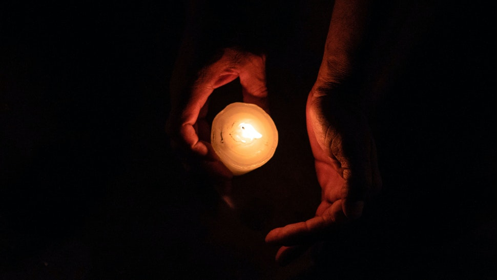 A member of the Pueblos Sin Fronteras, a pro-immigration advocacy group, lights a candle during a vigil to raise awareness of local police harassment and abuse of migrants, deported migrants and homeless in Tijuana, Baja California state, on September 16, 2018.