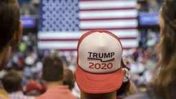 "An attendee wears a ""Trump 2020"" hat before the start of a rally with U.S. President Donald Trump in Wilkes-Barre, Pennsylvania, U.S., on Thursday, Aug. 2, 2018."