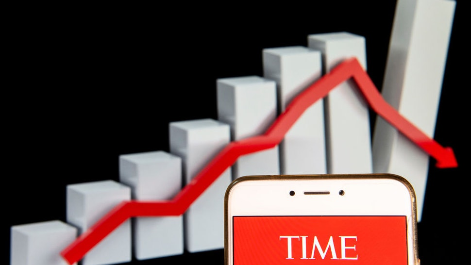 n this photo illustration, the American weekly news magazine and news website Time logo is seen displayed on an Android mobile device with a decline loses graph in the background.
