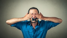 Portrait Of Scared Mid Adult Man With Black Adhesive Tape On Mouth Covering Eyes Against Gray Background - stock photo