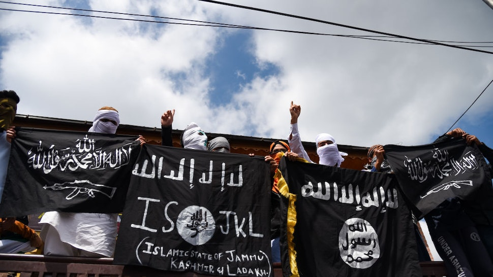 Kashmiri Protesters hold ISIS flags while making gestures during a protest in Srinagar. Indian forces in Srinagar used teargas smoke canisters and bullets to disperse hundreds of Protesters who took to streets after Eid-ul-Fitr prayers protesting against the Indian Rule in the region.
