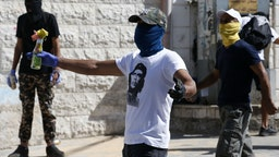 Masked Palestinian protesters throw molotov cocktails at Israeli security forces amidst clashes following Friday prayers in the Jerusalem Arab neighbourhood of Issawiya on June 28, 2019, after a Palestinian demonstrator died from injuries sustained the previous day.