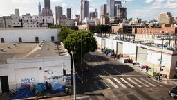 A man walks past a homeless tent encampment in Skid Row on September 16, 2019 in Los Angeles, California.