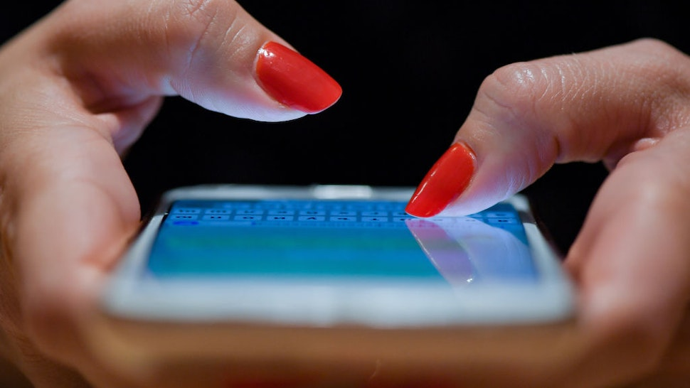 A woman with red fingernails writes a message on her smartphone.