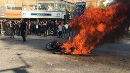 Iranian protesters gather around a burning motorcycle during a demonstration against an increase in gasoline prices in the central city of Isfahan, on November 16, 2019. - One person was killed and others injured in protests across Iran, hours after a surprise decision to increase petrol prices by 50 percent for the first 60 litres and 300 percent for anything above that each month, and impose rationing. Authorities said the move was aimed at helping needy citizens, and expected to generate 300 trillion rials ($2.55 billion) per annum.