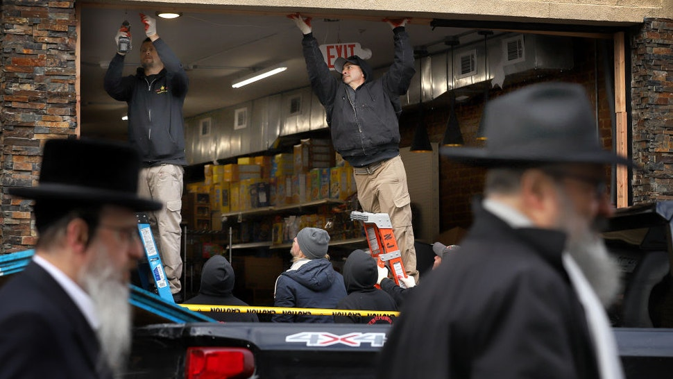 JERSEY CITY, NJ - DECEMBER 11: Recovery and clean up crews work the scene in the aftermath of a mass shooting at the JC Kosher Supermarket on December 11, 2019 in Jersey City, New Jersey. Six people, including a Jersey City police officer and three civilians were killed in a deadly, hours-long gun battle between two armed suspects and police on Tuesday in a standoff and shootout in a Jewish market that appears to have been targeted, according to Jersey City Mayor Steven Fulop.