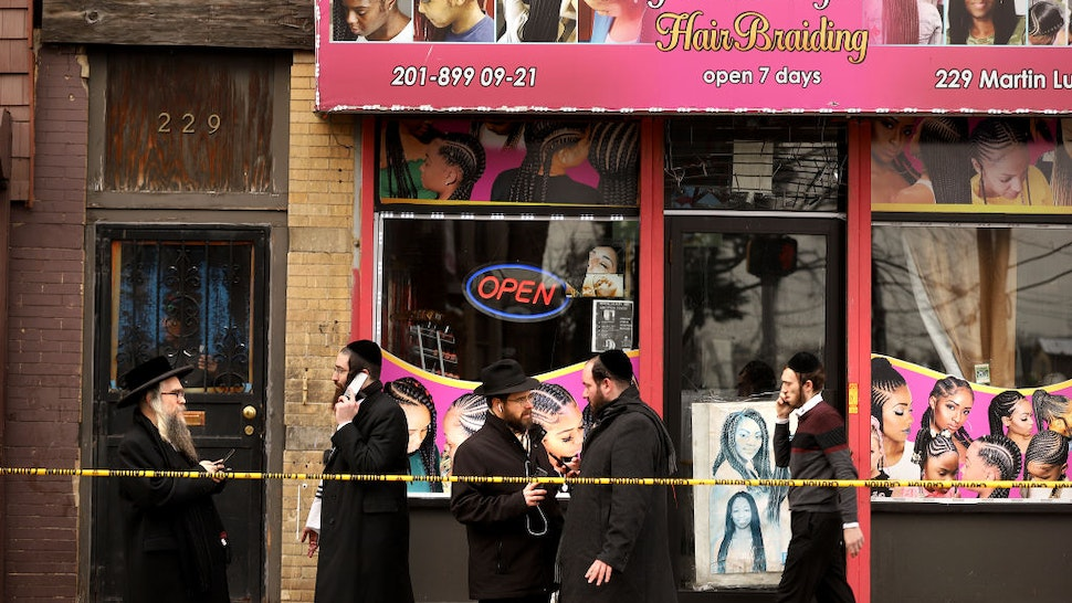 Members of the Jewish community pass by near the scene of a mass shooting at the JC Kosher Supermarket on December 11, 2019 in Jersey City, New Jersey.