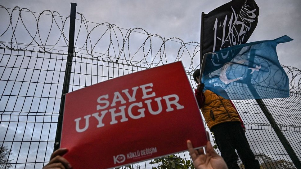"""A supporters of China's Muslim Uighur minority holds a placard reading """"Save Uighur"""" as a boy waves the flag of East Turkestan and an Islamic black flag on December 13, 2019 during a demostration in front of China Consulate in Istanbul."""