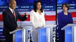 Democratic presidential candidate Sen. Cory Booker (D-NJ) speaks as Rep. Tulsi Gabbard (D-HI) and Sen. Amy Klobuchar (D-MN) (R) listen during the Democratic Presidential Debate at Tyler Perry Studios November 20, 2019 in Atlanta, Georgia.