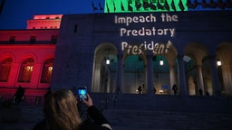 A message pro-impeachment is projected on the facade of the City Hall building before the start of a protest in Los Angeles on December 17, 2019.