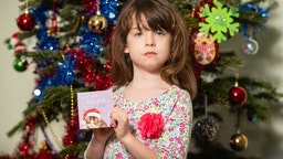 Florence Widdicombe, 6, at her home in Tooting, south London, holding a Tesco Christmas card from the same pack as a card she found contained a message from a Chinese prisoner.