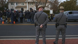 Two police officers stand guard as the press gathers outside a rabbi's home where a machete attack that took place earlier during the Jewish festival of Hanukkah, in Monsey, New York, on December 29, 2019. - An intruder stabbed and wounded five people at a rabbi's house in New York during a gathering to celebrate the Jewish festival of Hanukkah late on December 28, 2019, officials and media reports said. Local police departments, speaking to AFP, declined to give the number of people injured, but a suspect has been taken into custody and a vehicle safeguarded, an NYPD spokesman said. (Photo by Kena Betancur / AFP) (Photo by KENA BETANCUR/AFP via Getty Images)