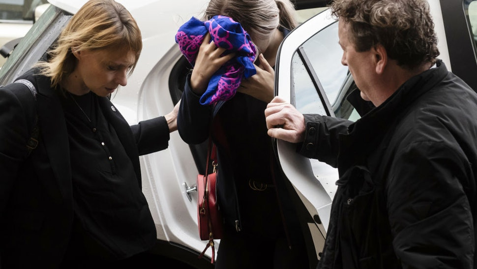 A British teenager (C) accused of falsely claiming she was raped by Israeli tourists, covers her face as she arrives for her trial at the Famagusta District Court in Paralimni in eastern Cyprus, on December 30, 2019.