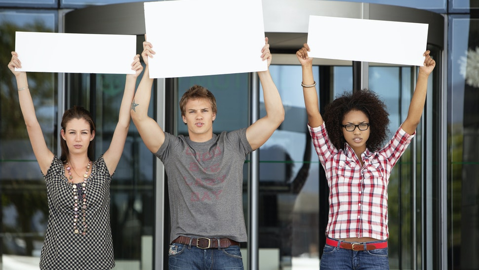 Three friends protesting with blank placards - stock photo