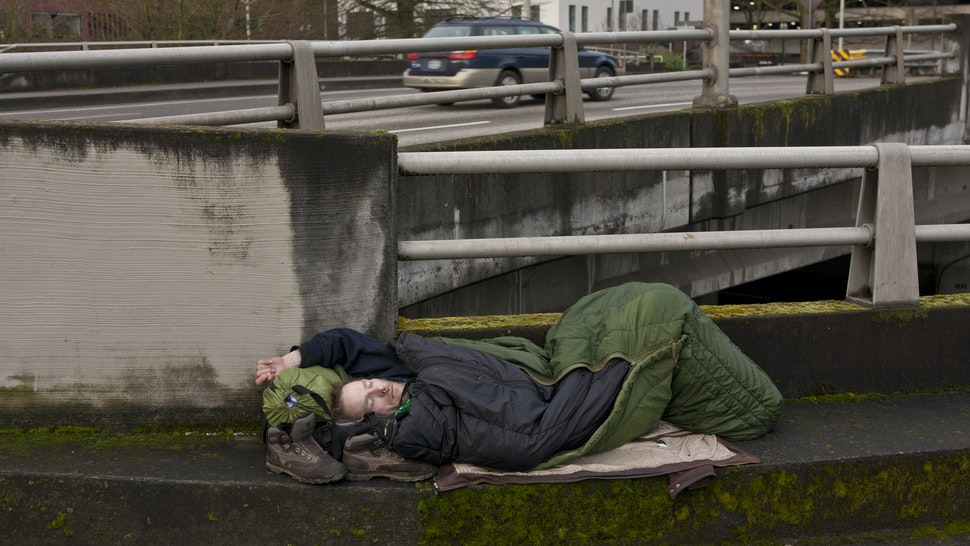"""ORTLAND, OR - FEBRUARY 11: A homeless man sleeps on a downtown roadway overpass on February 11, 2012 in Portland, Oregon. Portland has embraced its national reputation as a city inhabited by weird, independent people, as underscored in the dark comedy IFC TV show """"Portlandia."""" (Photo by George Rose/Getty Images)"""
