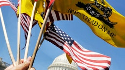U.S. flags and Gadsden flags fly in the breeze as Americans For Prosperity hold a tea party rally outside at the Capitol to emphasize their desire for huge spending cuts in the budget, April, 06, 2011 in Washington, DC.