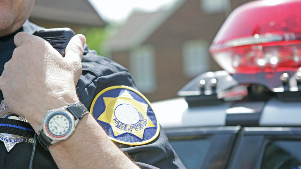 Police officer using radio to call for backup - stock photo