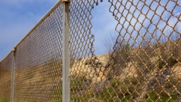 Fence with hole in California desert.