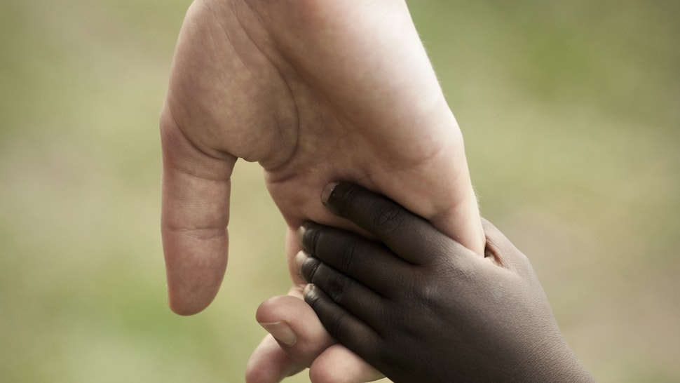 Hand of white adult and black child - stock photo