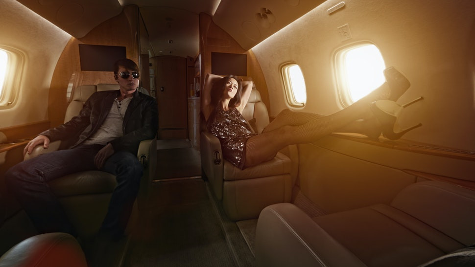 Young couple flying on private jet - stock photo
