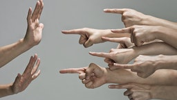Multiple white hands are pointing index fingers from the right to the left at one set of hands. The pair of hands that are being pointed at are up in a defensive pose, with fingers to the sky and palms towards the pointing fingers.