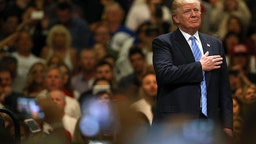 Donald Trump stands for the Pledge of Allegiance before speaking at a rally on May 25, 2016 in Anaheim, California.