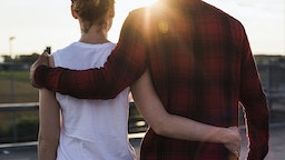 Young couple arm in arm at sunset - stock photo