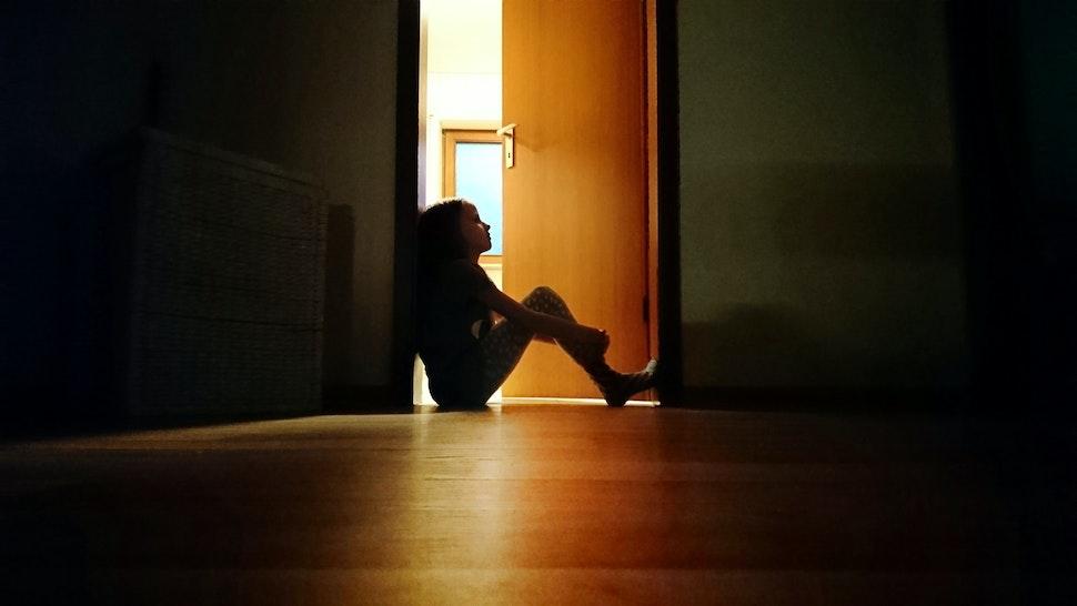 Backlit child sitting in a dark doorway in contemplation - stock photo