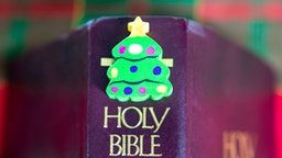 TORONTO, ONTARIO, CANADA - 2018/12/02: A small Christmas tree object over the Holy Bible. Christian origins of the Christmas holiday.