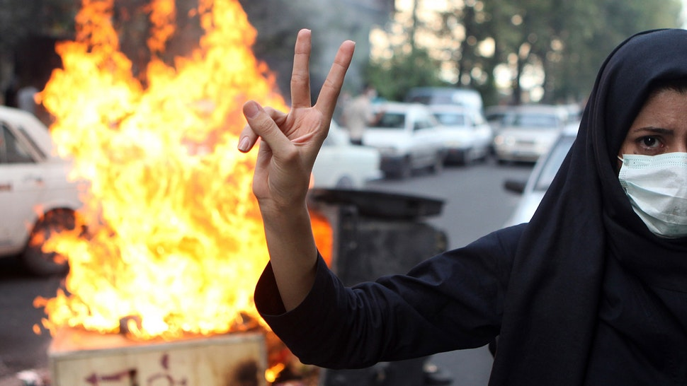 A woman protestor makes a V sign while standing in front of burning rubbish on July 9, 2009 in Tehran, Iran. Following recent unrest in the wake of the disputed presidental elections, demonstrators were met by force and tear gas rounds fired by Iranian police and Basij as they defied government warnings to stage a march in commeration of the anniversary of bloody student unrest at Tehran University in 1999.
