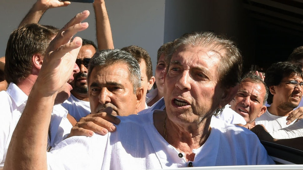 """Brazilian """"spiritual healer"""" Joao Teixeira de Faria (C), known as """"Joao de Deus"""" (John of God) is escorted by supporters, upon arrival at his """"healing center"""" Casa de Dom Inacio de Loyola, in Abadiania, 120 km southwest of Brasilia, state of Goias on December 12, 2018. - An internationally famous Brazilian """"spiritual healer"""" accused by hundreds of women of sexual abuse told his followers on Wednesday """"I am not guilty"""" of the allegations stacked against him. Police are starting to investigate complaints lodged by more than 450 women in Brazil following claims by a dozen of his followers aired by Globo TV and the O Globo newspaper last week that he forced them into sex acts under pretext of curing them of ailments. (Photo by EVARISTO SA / AFP)"""